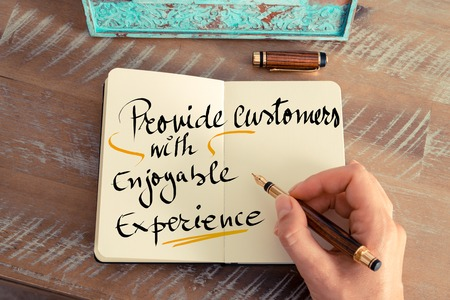 enjoyable: Retro effect and toned image of a woman hand writing a note with a fountain pen on a notebook. Handwritten text Provide Customers with Enjoyable Experience as business concept image