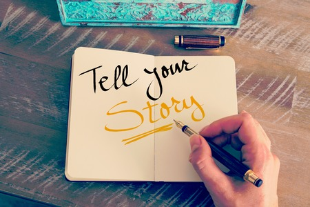 Retro effect and toned image of a woman hand writing a note with a fountain pen on a notebook. Handwritten text Tell Your Story as business concept image Banque d'images