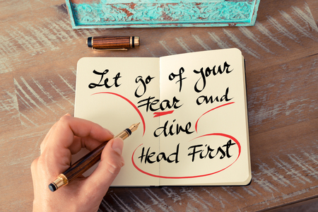 let go: Retro effect and toned image of a woman hand writing a note with a fountain pen on a notebook. Handwritten text Let Go Of Your Fear and Dive Head First as business concept image