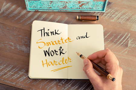 harder: Retro effect and toned image of a woman hand writing a note with a fountain pen on a notebook. Handwritten text Think Smarter and Work Harder as business concept image Stock Photo