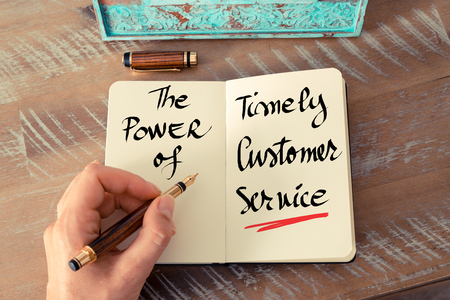 timely: Retro effect and toned image of a woman hand writing a note with a fountain pen on a notebook. Handwritten text The Power Of Timely Customer Service as business concept image