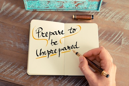 unprepared: Retro effect and toned image of a woman hand writing a note with a fountain pen on a notebook. Handwritten text Prepare To Be Unprepared as business concept image