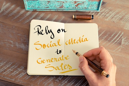 rely: Retro effect and toned image of a woman hand writing a note with a fountain pen on a notebook. Handwritten text Rely On Social Media To Generate Sales as business concept image