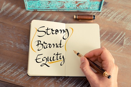 equidad: Retro effect and toned image of a woman hand writing a note with a fountain pen on a notebook. Handwritten text Strong Brand Equity as business concept image
