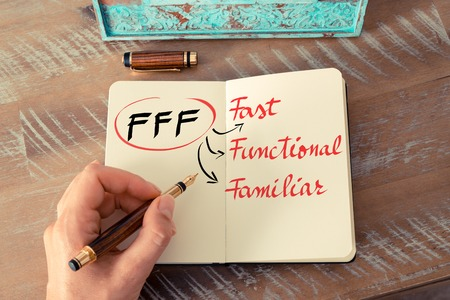 familiar: Retro effect and toned image of a woman hand writing a note with a fountain pen on a notebook. Acronym FFF as Fast, Functional, Familiar as business concept image
