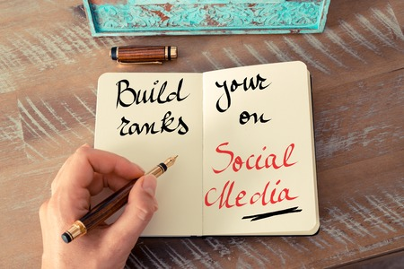 in the ranks: Retro effect and toned image of a woman hand writing a note with a fountain pen on a notebook. Handwritten text Build Your Ranks On Social Media as business concept image