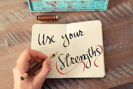 Retro effect and toned image of a woman hand writing a note with a fountain pen on a notebook. Handwritten text Use Your Strengths as business concept image