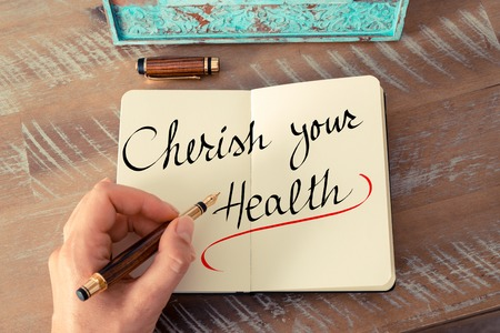 cherish: Retro effect and toned image of a woman hand writing a note with a fountain pen on a notebook. Handwritten text Cherish Your Health as business concept image
