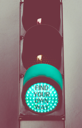 find your way: Close up on green traffic light with message FIND YOUR OWN WAY. Motivational concept image with vintage filter applied