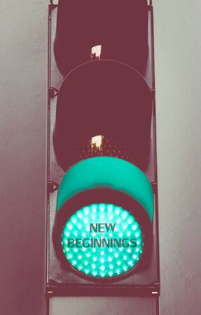 new beginnings: Close up on green traffic light with message NEW BEGINNINGS. Motivational concept image with vintage filter applied
