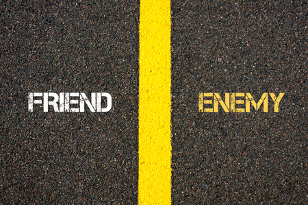 Antonym concept of FRIEND versus ENEMY written over tarmac, road marking yellow paint separating line between words Stock Photo