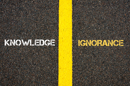 ignorance: Antonym concept of KNOWLEDGE versus IGNORANCE written over tarmac, road marking yellow paint separating line between words