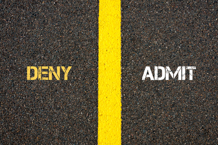 deny: Antonym concept of DENY versus ADMIT written over tarmac, road marking yellow paint separating line between words Stock Photo