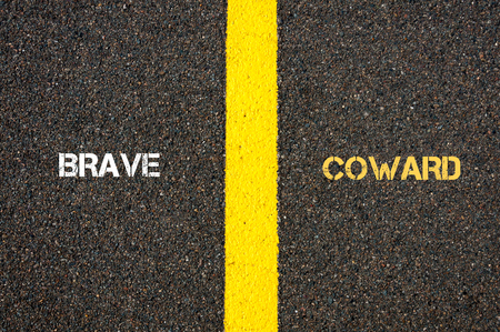 coward: Antonym concept of BRAVE versus COWARD written over tarmac, road marking yellow paint separating line between words