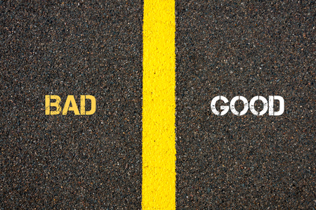 Antonym concept of BAD versus GOOD written over tarmac, road marking yellow paint separating line between words