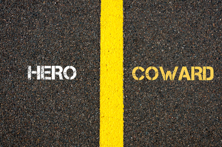 coward: Antonym concept of HERO versus COWARD written over tarmac, road marking yellow paint separating line between words