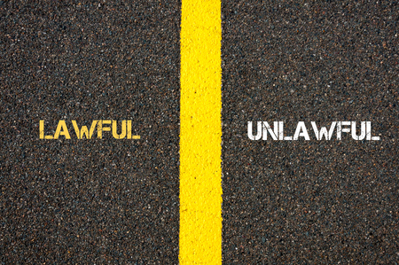 unlawful: Antonym concept of LAWFUL versus UNLAWFUL written over tarmac, road marking yellow paint separating line between words Stock Photo
