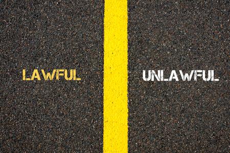 lawful: Antonym concept of LAWFUL versus UNLAWFUL written over tarmac, road marking yellow paint separating line between words Stock Photo