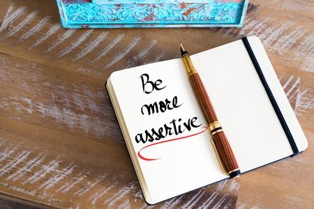 Retro effect and toned image of a fountain pen on a notebook. Handwritten text Be More Assertive as business concept image