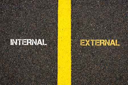 Antonym concept of INTERNAL versus EXTERNAL written over tarmac, road marking yellow paint separating line between words Reklamní fotografie