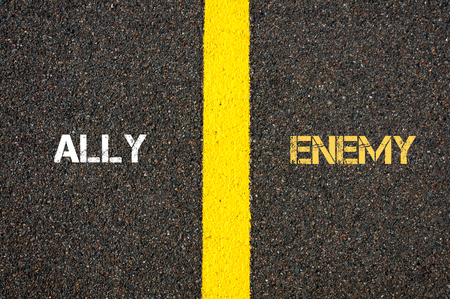 an ally: Antonym concept of ALLY versus ENEMY written over tarmac, road marking yellow paint separating line between words