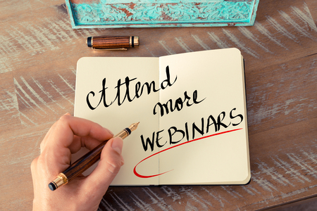 attend: Retro effect and toned image of a woman hand writing a note with a fountain pen on a notebook. Handwritten text Attend More Webinars as business concept image