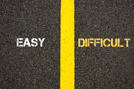 contradiction: Antonym concept of EASY versus DIFFICULT written over tarmac, road marking yellow paint separating line between words
