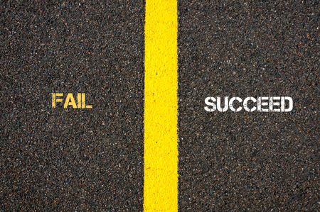 contradiction: Antonym concept of FAIL versus SUCCEED written over tarmac, road marking yellow paint separating line between words