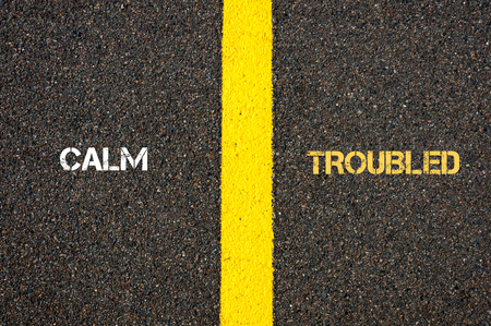 yellow line: Antonym concept of CALM versus TROUBLED written over tarmac, road marking yellow paint separating line between words
