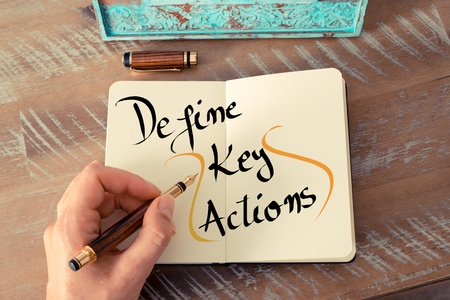 define: Retro effect and toned image of a woman hand writing a note with a fountain pen on a notebook. Handwritten text Define Key Actions as business concept image
