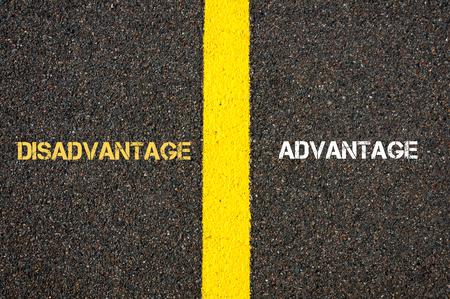 disadvantage: Antonym concept of DISADVANTAGE versus ADVANTAGE written over tarmac, road marking yellow paint separating line between words