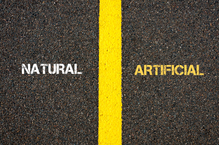 contradiction: Antonym concept of NATURAL versus ARTIFICIAL written over tarmac, road marking yellow paint separating line between words Stock Photo