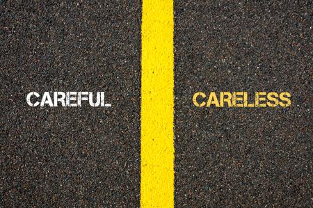 careless: Antonym concept of CAREFUL versus CARELESS written over tarmac, road marking yellow paint separating line between words