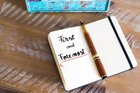 foremost: Retro effect and toned image of a fountain pen on a notebook. Handwritten text First and Foremost as business concept image