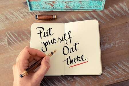put forward: Retro effect and toned image of a woman hand writing a note with a fountain pen on a notebook. Handwritten text Put Yourself Out There as business concept image