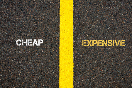Antonym concept of CHEAP versus EXPENSIVE written over tarmac, road marking yellow paint separating line between words