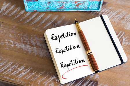 repetition: Retro effect and toned image of a fountain pen on a notebook. Handwritten text Repetition, Repetition, Repetition as business concept image