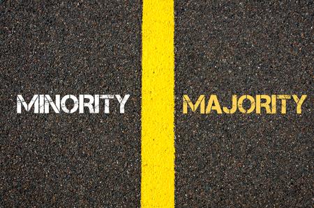 majority: Antonym concept of MINORITY versus MAJORITY written over tarmac, road marking yellow paint separating line between words Stock Photo