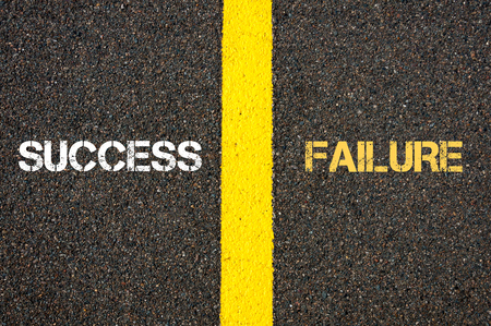 Antonym concept of SUCCESS versus FAILURE written over tarmac, road marking yellow paint separating line between words