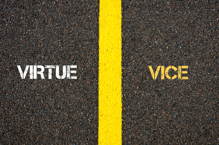 virtue: Antonym concept of VIRTUE versus VICE written over tarmac, road marking yellow paint separating line between words