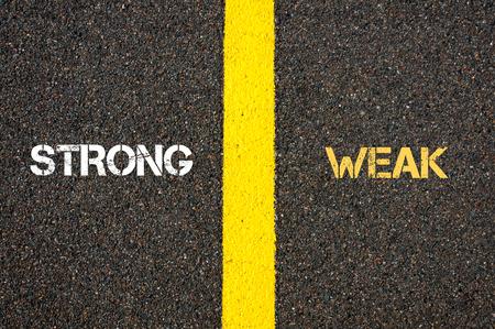 weak: Antonym concept of STRONG versus WEAK written over tarmac, road marking yellow paint separating line between words Stock Photo