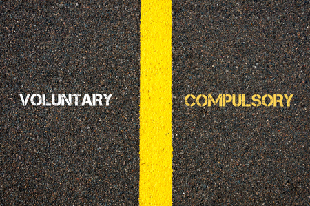 Antonym concept of VOLUNTARY versus COMPULSORY written over tarmac, road marking yellow paint separating line between words Stock Photo
