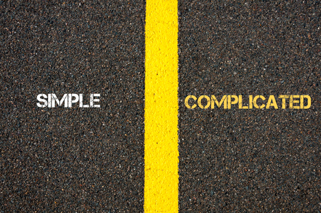Antonym concept of SIMPLE versus COMPLICATED written over tarmac, road marking yellow paint separating line between words