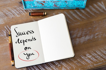 depends: Retro effect and toned image of a woman hand writing a note with a fountain pen on a notebook. Handwritten text Success Depends On You as business concept image