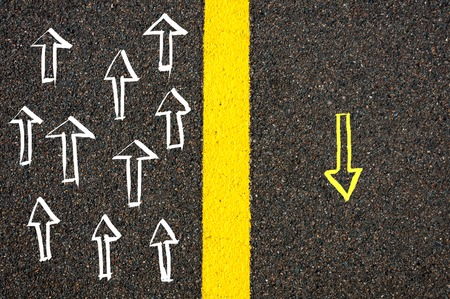 contradiction: Road marking yellow paint dividing line between arrows going in different directions, Find Your Own Way concept Stock Photo