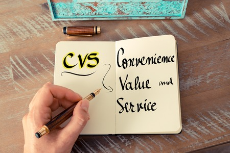 Retro effect and toned image of a woman hand writing a note with a fountain pen on a notebook. Business Acronym CVS as Convenience Value and Service as business concept image