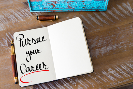 pursue: Retro effect and toned image of a woman hand writing a note with a fountain pen on a notebook. Handwritten text Pursue Your Career as business concept image