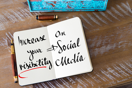 increase visibility: Retro effect and toned image of a woman hand writing a note with a fountain pen on a notebook. Handwritten text Increase Your Visibility On Social Media as business concept image Stock Photo