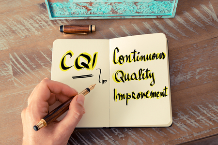pen quality: Retro effect and toned image of a woman hand writing a note with a fountain pen on a notebook. Business Acronym CQI as Continuous Quality Improvement as business concept image