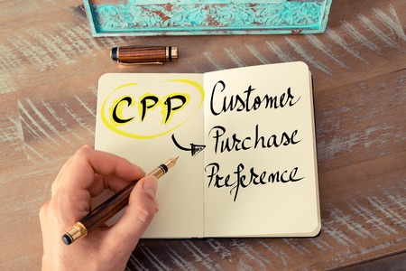 preference: Retro effect and toned image of a woman hand writing a note with a fountain pen on a notebook. Business Acronym CPP as Customer Purchase Preference as business concept image